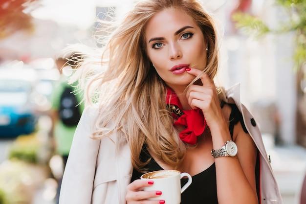 Zamyślona dama o ciemnoniebieskich oczach pozująca z filiżanką herbaty relaksująca po ciężkim tygodniu