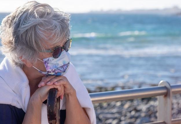Zamyślona dojrzała kobieta o siwych włosach, nosząca maskę ochronną. siedząc na zewnątrz na plaży z horyzontem nad morzem, trzymając laskę spacerową