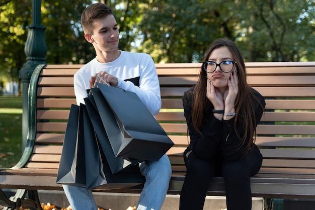Zamyślona dziewczyna i wesoły facet z torby na zakupy na ławce w parku. nieudane zakupy.