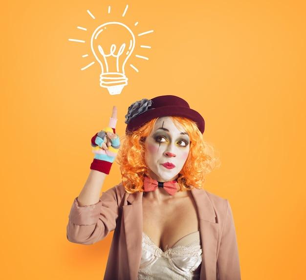 Zamyślona dziewczyna klauna wymyśla nowy pomysł. żółte tło.