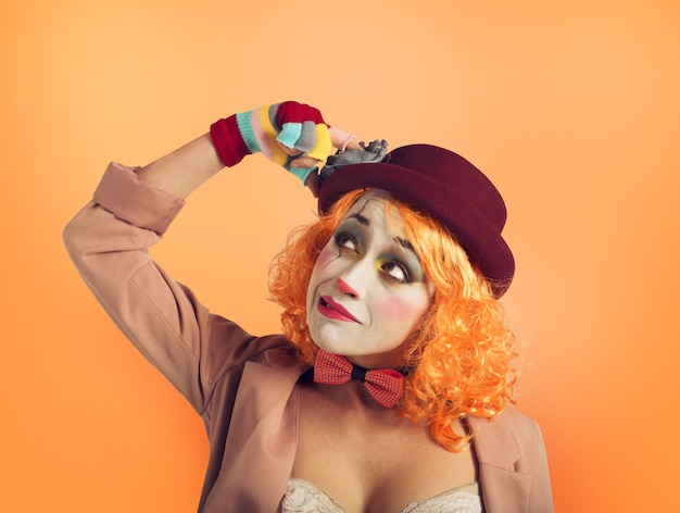Zamyślona dziewczyna klauna ze zbyt wieloma pytaniami. pomarańczowe tło