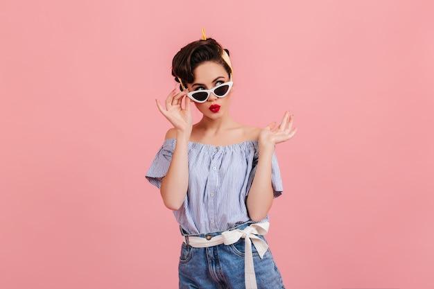 Zamyślona dziewczyna pinup w okulary stojąc na różowym tle. strzał studio młoda dama brunetka w letnim stroju.