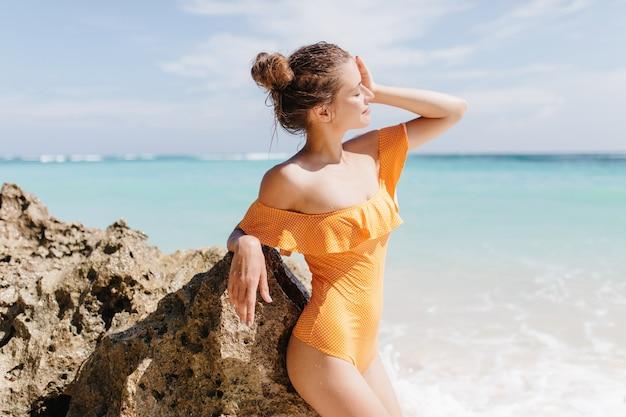 Zamyślona dziewczyna stojąca w pobliżu skały morskiej i ciesząc się słońcem. zewnątrz zdjęcie atrakcyjnej białej kobiety w stroju kąpielowym vintage chłodzenie w ośrodku.