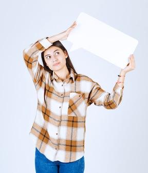 Zamyślona dziewczyna trzyma pustą ramkę mowy na białej ścianie.