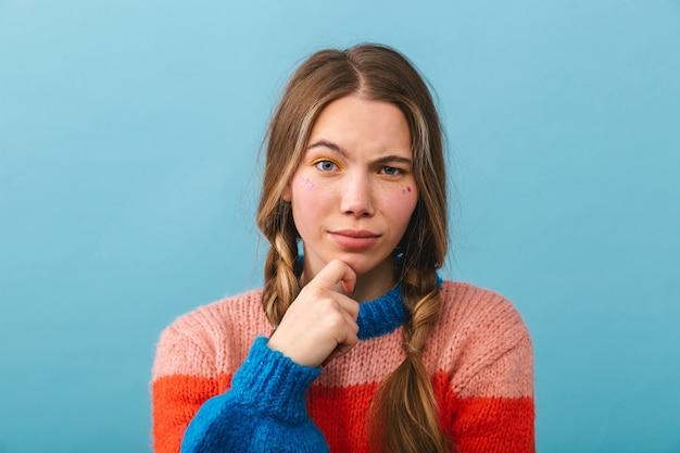 Zamyślona dziewczyna ubrana w sweter stojący na białym tle, myśląc