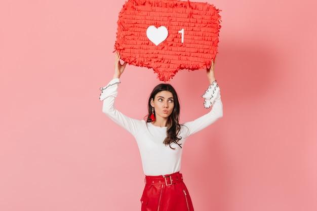 """Zamyślona dziewczyna w czerwonym stroju trzyma znak """"like"""" z sieci społecznościowej. brunetka ślicznie gryzie wargę."""
