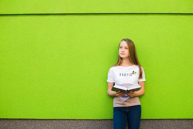 Zamyślona dziewczyna z podręcznikiem