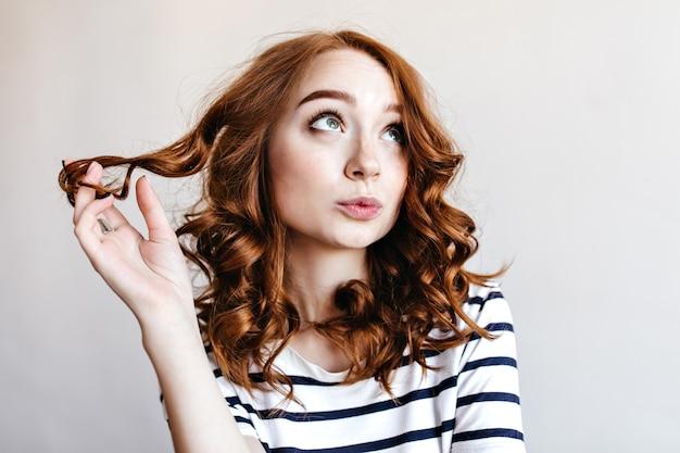 Zamyślona dziewczyna ze stawianiem piękne rude włosy. czarująca stylowa kobieta z kręconą fryzurą.