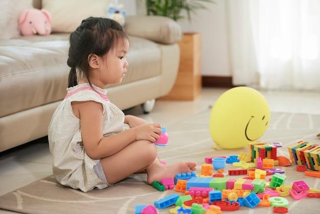 Zamyślona dziewczynka siedzi na podłodze w salonie i patrzy na stos kolorowych zabawek k...