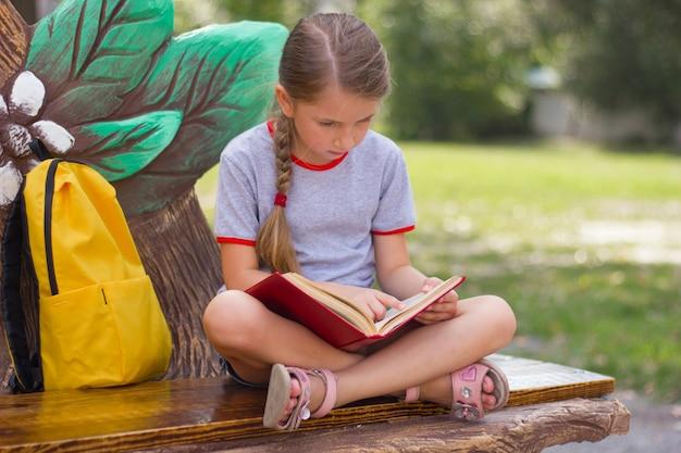 Zamyślona dziewczynka siedzi w parku i czyta książkę powrót do koncepcji szkoły