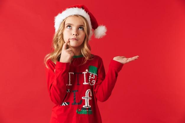Zamyślona dziewczynka ubrana w świąteczny kostium stojący na białym tle, prezentując miejsce na kopię