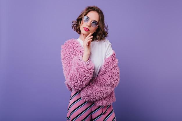 Zamyślona elegancka kobieta w okularach przeciwsłonecznych odwracająca wzrok podczas sesji zdjęciowej na fioletowej ścianie. kryty zdjęcie zainteresowanej dziewczyny z krótką fryzurą nosi jasne ubrania.