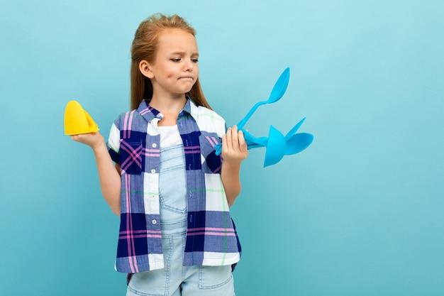 Zamyślona europejska dziewczyna trzyma w rękach rękawice kuchenne i sztućce na jasnoniebieskiej ścianie.