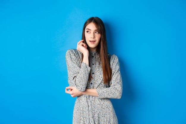 Zamyślona kaukaska dziewczyna z długimi naturalnymi włosami, ubrana w sukienkę vintage, wyglądającą na lewo z zamyśloną twarzą...
