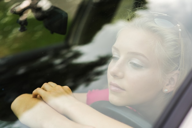 Zamyślona kobieta przytula kierownicę