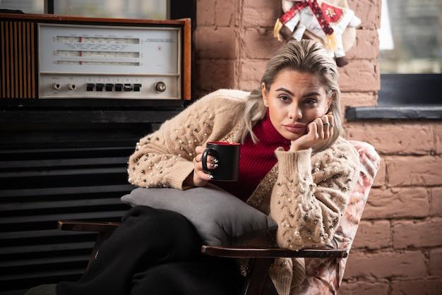 Zamyślona kobieta siedzi i czyta książkę i pije kawę