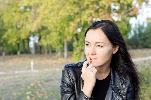Zamyślona kobieta siedzi na świeżym powietrzu na wsi, myśląc i wpatrując się w dal