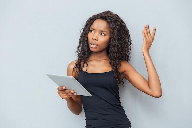 Zamyślona kobieta trzymająca komputer typu tablet nad szarą ścianą
