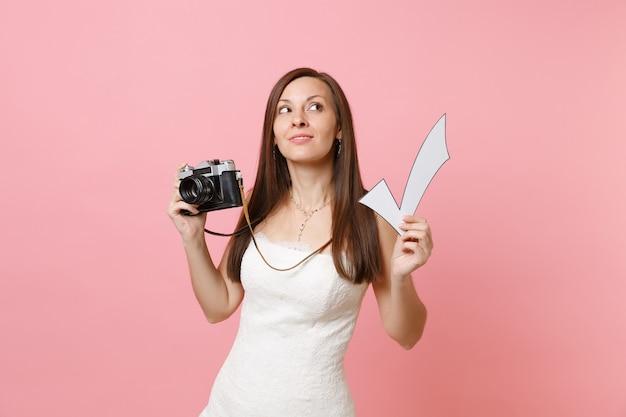 Zamyślona kobieta w białej sukni patrząc w górę trzymaj retro vintage aparat fotograficzny i zaznacz zaznaczenie wybierając personel fotografa