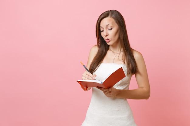 Zamyślona kobieta w białej sukni, pisząca notatki w pamiętniku, zeszycie