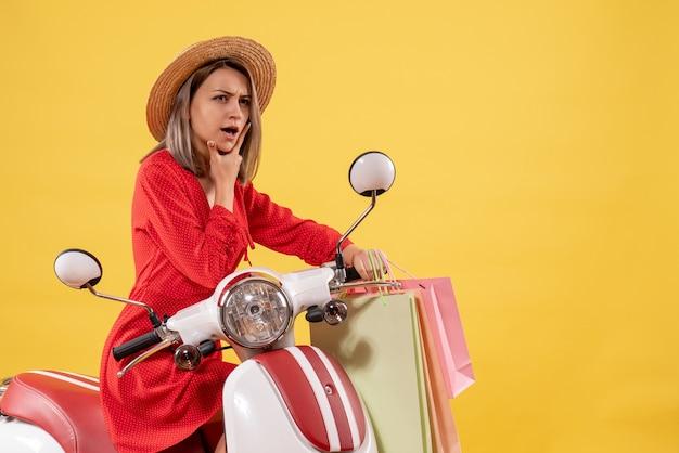 Zamyślona kobieta w czerwonej sukience na motorowerze trzymająca torby na zakupy