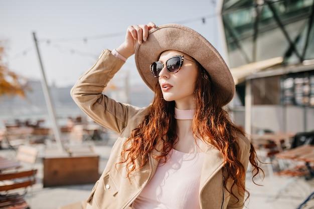 Zamyślona kobieta z długimi brązowymi włosami, patrząc w górę, czeka przyjaciel obok kawiarni na świeżym powietrzu