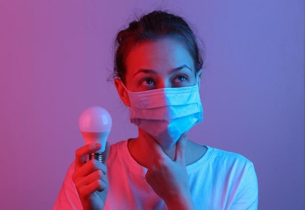 Zamyślona kobieta z medyczną maską na twarz trzyma żarówkę w czerwono-niebieskim neonowym świetle