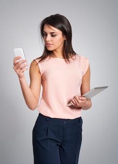Zamyślona kobieta ze sprzętem elektronicznym