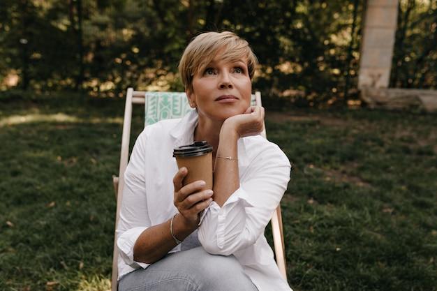 Zamyślona kobieta ze stylową blond fryzurą w białej fajnej bluzce i dżinsach, trzymając filiżankę kawy i patrząc w parku.