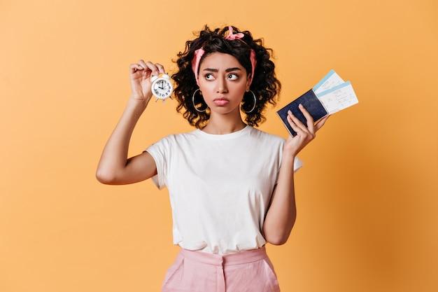 Zamyślona kręcona kobieta trzyma budzik i bilety lotnicze