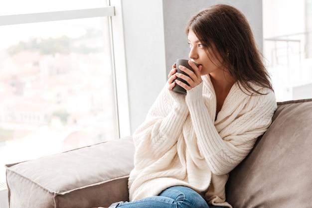 Zamyślona ładna młoda kobieta myśli i pije kawę w domu