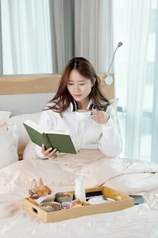 Zamyślona ładna młoda kobieta pije filiżankę cappuccino i czyta ciekawą książkę, siedząc na łóżku w domu