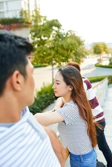Zamyślona ładna młoda kobieta stojąca na moście z przyjaciółmi i patrząca na miasto