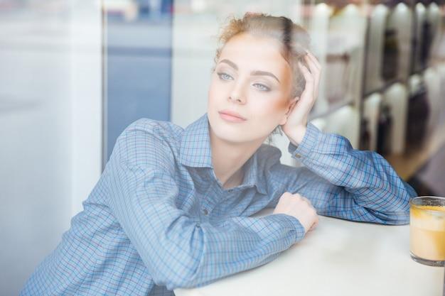 Zamyślona ładna młoda kobieta w niebieskiej koszuli siedzi i myśli w kawiarni