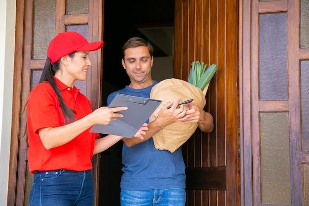 Zamyślona listonoszka trzymająca schowek i pokazująca dane w arkuszu zamówienia. atrakcyjny klient stojący, odbierający warzywa w papierowej torbie ze sklepu spożywczego. dostawa żywności i koncepcja poczty