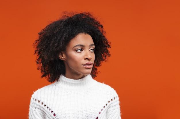 Zamyślona młoda afrykańska kobieta w swetrze stojąca na białym tle nad czerwoną ścianą, odwracająca wzrok
