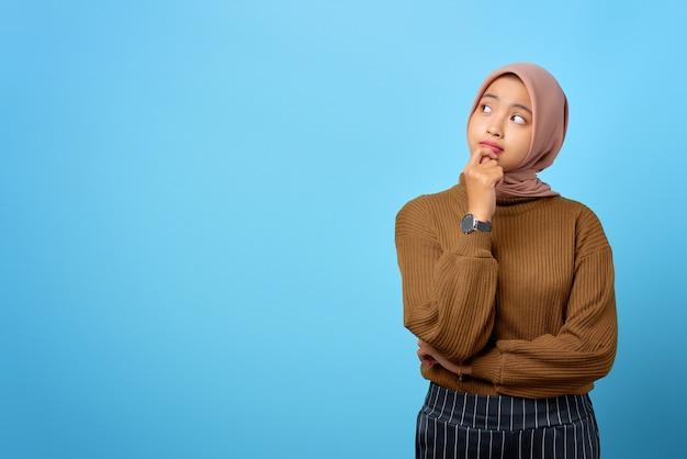Zamyślona młoda azjatka wygląda poważnie myśląc o pytaniu na niebieskim tle