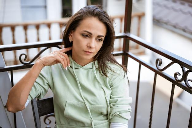 Zamyślona młoda brunetka w zwykłych ubraniach siedzi na krześle na balkonie latem