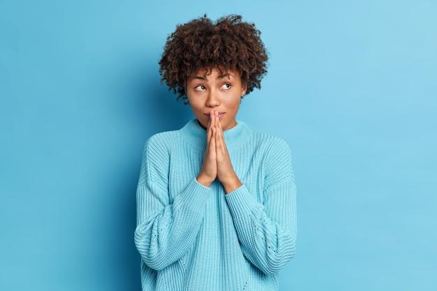 Zamyślona młoda ciemnoskóra dziewczyna z włosami afro trzyma dłonie razem i modli się do boga, wierzy w coś dobrego, ma wiarę dla lepszego życia, ubrana swobodnie