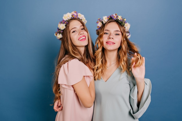 Zamyślona młoda dama z jasnymi kręconymi włosami obejmująca przyjaciółkę