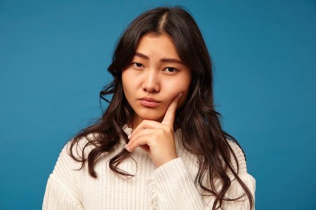 Zamyślona młoda, dość długowłosa azjatycka kobieta z naturalnym makijażem, trzymając palec wskazujący