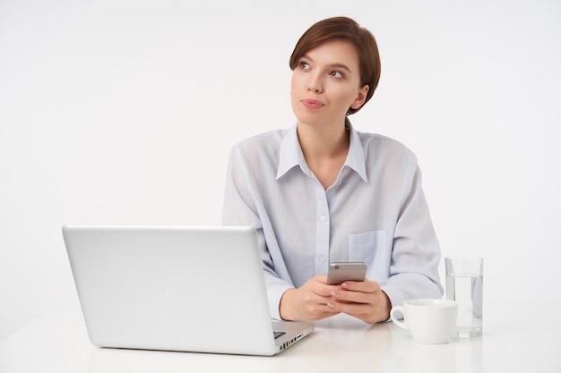 Zamyślona młoda, dość krótkowłosa brunetka dama z krótką modną fryzurą, patrząc w zamyśleniu z założonymi ustami i trzymającą smartfona w rękach, odizolowana na białym