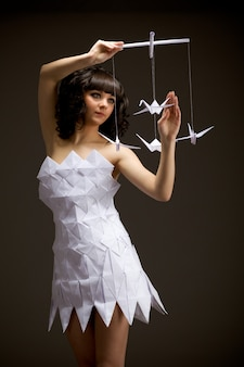 Zamyślona młoda dziewczyna w sukience origami trzyma w rękach ptaka origami