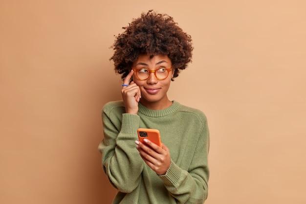 Zamyślona młoda etniczna kobieta trzyma palec wskazujący na skroni próbuje zapamiętać numer telefonu, na którym ktoś trzyma nowoczesny smartfon i skupiony na sobie nosi okulary zwykły sweter
