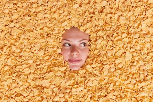 Zamyślona młoda europejka odwraca wzrok z zamyślonym wyrazem twarzy zakopana w płatkach zbożowych ma zdrowe odżywianie przygotowuje śniadanie w otoczeniu płatków kukurydzianych. dieta i zbilansowana koncepcja odżywiania
