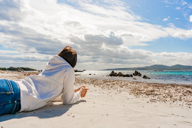 Zamyślona młoda kobieta nie do poznania, leżąc na łokciach na piasku zimowego oceanu, patrząc na horyzont i dramatyczne pochmurne niebo na wodzie w surrealistycznym scenariuszu. przemyślana dorywczo ubrana dziewczyna w dżinsach