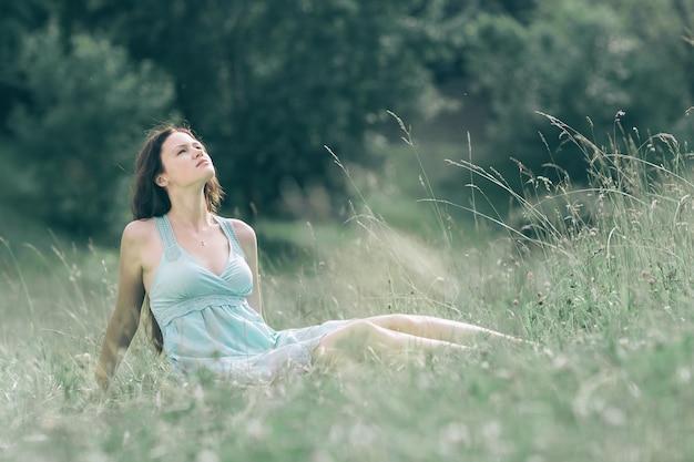 Zamyślona młoda kobieta patrząca na letnie niebo .zdjęcie z miejscem na kopię