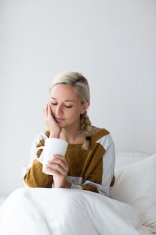 Zamyślona młoda kobieta siedzi na łóżku z filiżanką