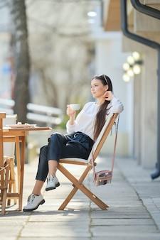 Zamyślona młoda kobieta siedzi na tarasie kawiarni w słoneczny dzień i pije kawę.