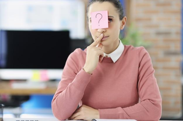 Zamyślona młoda kobieta siedzi przy stole z naklejką ze znakiem zapytania na czole kobiety